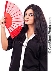 Portrait of a brunette young woman holding red fan against...