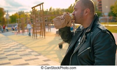 Portrait of a brutal man illegally drinking beer on the kid's playground. He put the beer can into a paper bag. Slow motion