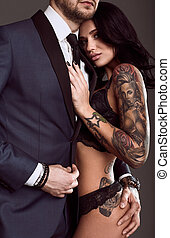 Portrait of a brutal man in suit and sexy girl