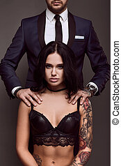 Portrait of a brutal man in suit and sexy girl - Portrait of...