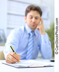 Portrait of a business man filling a form, focus on hand ...