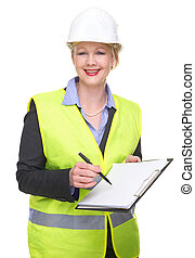 Portrait of a business woman in safety vest and hardhat writing on blank clipboard