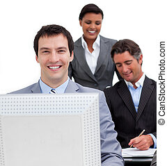 Portrait of a businessman and his team working at a computer