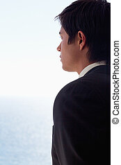 Portrait of a businessman day dreaming while looking at the ...