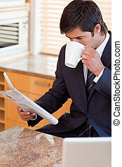 Portrait of a businessman drinking coffee while reading the news in his kitchen