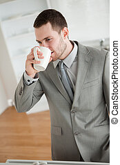 Portrait of a businessman drinking coffee in his kitchen