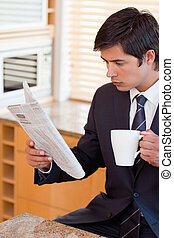 Portrait of a businessman drinking tea while reading the news