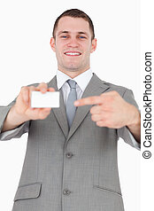 Portrait of a businessman pointing at a blank business card