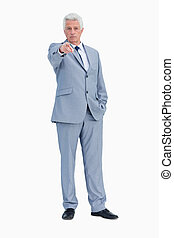 Portrait of a businessman pointing to someone against white...
