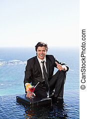 Portrait of a businessman posing with a cocktail on a briefcase