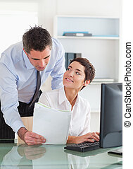 Portrait of a businessman showing a document to his colleague