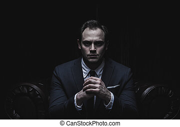 Portrait of a businessman sitting on armchair black...