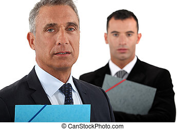 Portrait of a businessman with his assistant trailing behind...