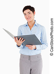 Portrait of a businesswoman holding a binder against a white...