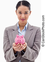 Portrait of a businesswoman holding a piggy bank