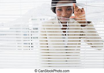 Portrait of a businesswoman peeking through blinds