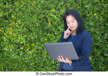 portrait of a businesswoman standing and using laptop on tree wall.