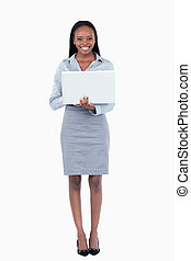 Portrait of a businesswoman using a laptop while standing up...