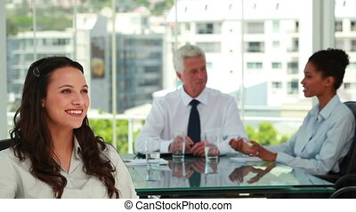 Portrait of a businesswoman with co-workers in background in...