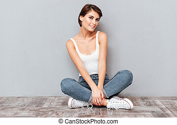 Portrait of a casual happy woman sitting on the floor