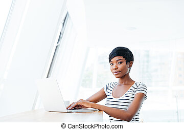 Portrait of a casual smiling african businesswoman using laptop computer