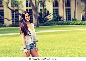 Portrait of a casual smiling young pretty Asian girl outdoors- filter