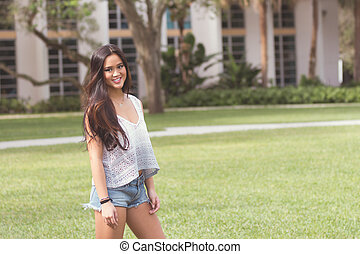 Portrait of a casual smiling young pretty Asian girl outdoors - filter