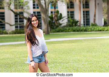 Portrait of a casual smiling young pretty Asian girl outdoors