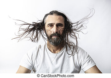 portrait of a caucasian man with beard and fluttering long hair.