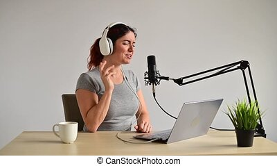 Portrait of a Caucasian woman in headphones is broadcasting on a white background. Leading girl at the radio station.
