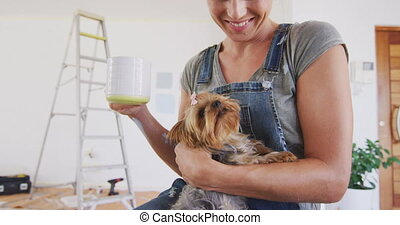 A Caucasian woman spending time at home, renovating her house, social distancing and self isolation in quarantine lockdown during coronavirus covid 19 epidemic, with a dog sitting on her lap
