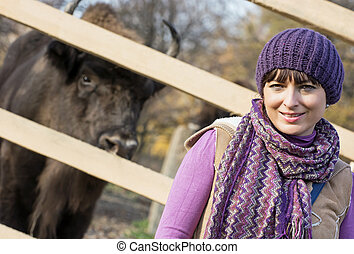 Portrait of a caucasian woman with the European bison (Bison bonasus) behind the fence.