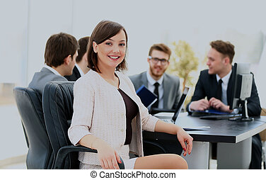 Portrait of a charismatic woman at a meeting while her team working in the background.