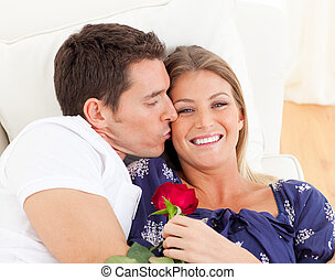 Portrait of a charming man kissing his wife lying on sofa