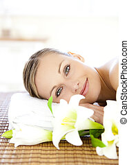 Portrait of a charming woman lying on a massage table smiling at the camera in a health spa