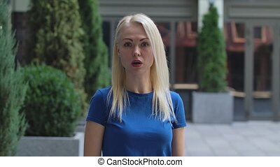 Portrait of a charming young woman looking at the camera and talking to someone. Blonde in a blue blouse outdoors on the background of the street. Slow motion. Close up.