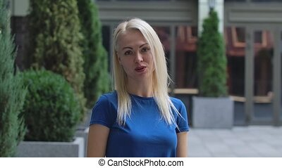 Portrait of a charming young woman looking at the camera and talking to someone rejoicing and smiling. Blonde in a blue blouse outdoors on the background of the street. Slow motion. Close up.