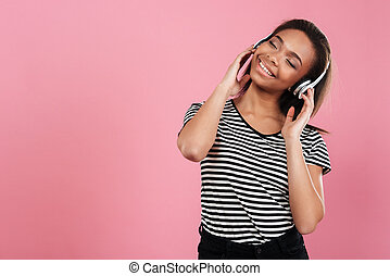 Portrait of a cheerful african woman listening music with headphones