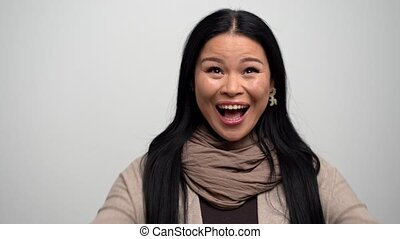 Portrait of a cheerful Asian woman showing her happiness - ...