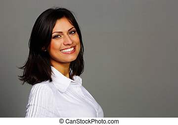 Portrait of a cheerful beautiful woman on gray background