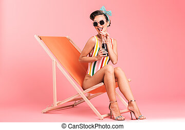 Portrait of a cheerful brunette pin-up girl in swimsuit