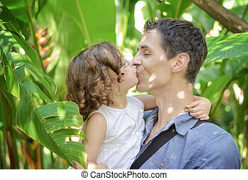 Portrait of a cheerful child kissing her father