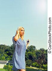 Portrait of a cheerful cute woman listening music