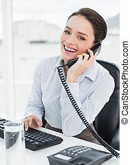 Portrait of a cheerful elegant businesswoman using landline phone at office desk