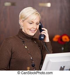cheerful female receptionist using telephone - portrait of a...