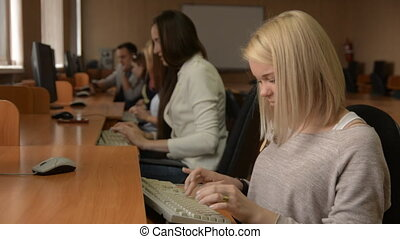 Portrait of a cheerful female student working on the computer