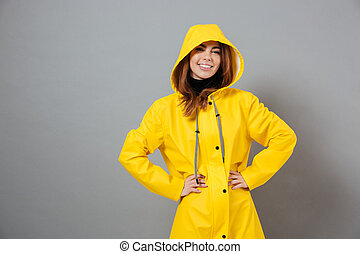 Portrait of a cheerful girl dressed in raincoat posing
