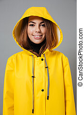 Portrait of a cheerful girl dressed in raincoat