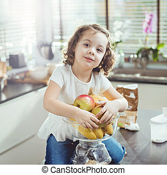 Portrait of a cheerful girl holding a bunch of fruit