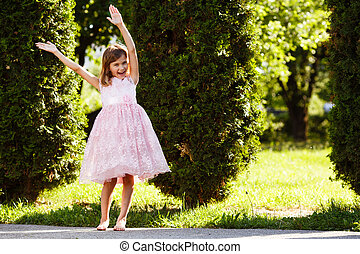 Portrait of a cheerful girl in a lush pink dress in the park.